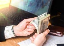 Een mens zit dobbelt en denkt over geld op een witte achtergrond Het concept het gokken Kansberekening Verlies in stock foto
