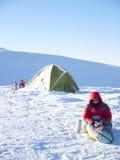 Een mens zit in een slaapzak dichtbij de tent en de sneeuwschoenen stock afbeelding
