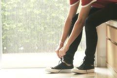 Een mens zit en bindt de schoen royalty-vrije stock afbeelding