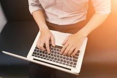 Een mens zit en gebruikend notitieboekje Stock Afbeeldingen