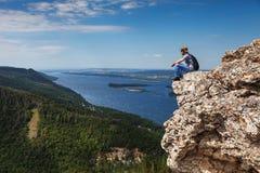 Een mens zit op een berg en bekijkt een mooie mening Royalty-vrije Stock Foto
