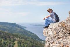 Een mens zit op een berg en bekijkt een mooie mening Royalty-vrije Stock Afbeelding
