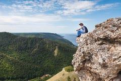 Een mens zit op een berg en bekijkt een mooie mening Stock Afbeelding