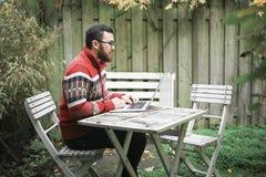 Een mens zit op de straat en het werken Stock Afbeelding
