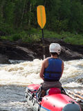 Een mens zit op een catamaran kleedde een reddingsvest en een helm Royalty-vrije Stock Afbeeldingen