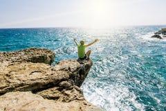 Een mens zit op een richel van rots boven het overzees bij Kaap Greco Cypr Stock Foto's