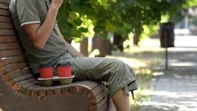 Een mens zit op houten bank in de steeg onder boom en drinkt koffie van rode kop stock videobeelden