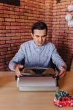 Een mens zit op een schrijfmachine in een feestelijke stemming met een glas stock afbeelding