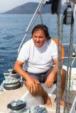 Een mens zit op zijn varend jacht Zakenman Royalty-vrije Stock Afbeelding
