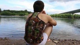 Een mens zit tegenover de rivier, mediteert en rookt op de achtergrond van de rivier en de brug stock footage