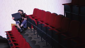 Een mens zit tussen de rijen van Rode stoelen op de vloer en het gebruiken van laptop stock video