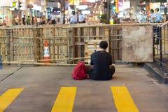 Een mens zit voor barrière, een straat het blokkeren demonstratie Royalty-vrije Stock Foto's