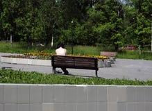 Een mens zonnebaadt in de zonzitting op de bank royalty-vrije stock afbeelding