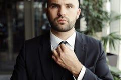 Een mens in een zwart kostuum maakt zijn band recht stock afbeelding