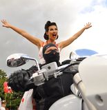Een mens in een zwart masker zit achter het wiel van een witte motorfiets achter hem zit een mooi meisje op een achtergrond van d royalty-vrije stock fotografie