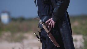 Een mens in zwarte die kleren met een mes wordt bewapend bevindt zich op de woestenij en bekijkt de hemel en voorwaarts stock footage