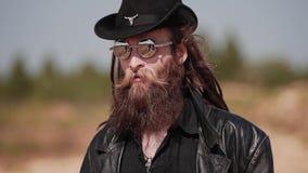 Een mens in zwarte kleren en een ernstige blik op de camera maakt zijn hoed met een mes recht stock footage