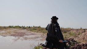 Een mens in een zwarte laag en hoed met een mes in zijn handen die de woestijn doornemen stock video