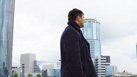 Een mens in een zwarte laag tegen een achtergrond van moderne gebouwen met meerdere verdiepingen stock videobeelden