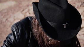 Een mens in een zwarte mantel die heft zijn hoofd op en onderzoekt de afstand hurkt stock videobeelden