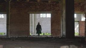 Een mens in een zwarte regenjas, een hoed en zwarte glazen, met een baard en dreadlocks is een grote ruimte verlaten fabriek stock footage