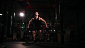 Een mens in zwarte sportkleding in de gymnastiek voert een oefening voor een zwaar detachement uit - een schok stock footage