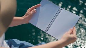 Een menselijk wezen met een hoed opent en sluit het notitieboekje schoonmaakt het water stock videobeelden