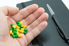 Een menselijke hand die groene en gele pillen naast een blocnote en een pen houden Dit beeld kan worden gebruikt om medicijn te v Royalty-vrije Stock Afbeeldingen