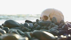 Een menselijke schedel op het strand, onder de golven van water 4k, langzame motie stock footage