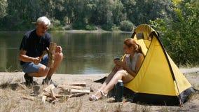 Een mensen hakkend hout dichtbij de tent Het meisje lacht zitting in een tent Wandeling, reis, groen toerismeconcept Gezond stock video