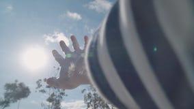 Een mensen` s hand bereikt voor de zon uit het autoraam stock video