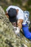 Een mensen` s hand die een rots beklimmen Het wit dient het beklimmen van magnesia in stock afbeeldingen