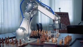 Een mensen` s hand en een robotachtig wapen vestigen stukken opnieuw terwijl het spelen van schaak