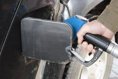 Een mensen` s hand houdt een bijtankend kanon bij een gas Stock Foto's