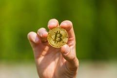 Een mensen` s hand houdt een gouden muntstuk bitcoin Royalty-vrije Stock Afbeelding