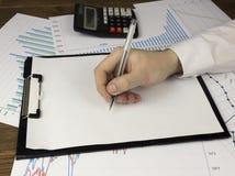 Een mensen` s hand houdt een pen op een leeg blad, een duiker, verbindingszaken royalty-vrije stock fotografie