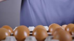 Een mensen` s hand neemt een volledig glas met gebroken eieren, langzame motie stock videobeelden