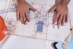 Een mensen` s hand trekt een bouwtekening stock fotografie