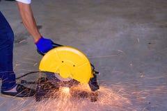 Een mensen scherp staal met een elektrische machine van de staalsnijder royalty-vrije stock afbeeldingen
