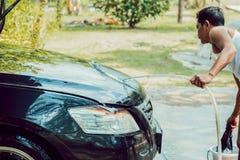 Een mensen schoonmakende auto met een water thuis stock foto's
