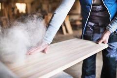 Een mensenarbeider in de timmerwerkworkshop, die met hout werken stock afbeelding