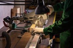 Een mensenbouwer zaagt een raad met een cirkelzaag in de workshop stock afbeelding