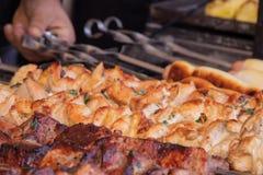 Een mensengebraden gerechten een barbecue van varkensvleesvlees en een grill op de rug van het kippenvlees stock foto