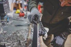 Een mensenhersteller in de dienst die van de workshopski de het glijden oppervlakte van de ski herstellen bij Skibankschroef In h stock foto's