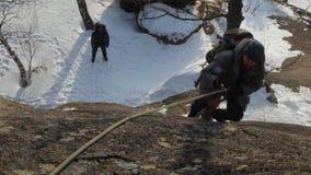 Een mensenklimmer beklimt de kabel tot de bovenkant stock footage