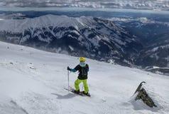 Een mensenskiër die het beste spoor voor freeride vinden Een skiër die neer aan de vallei kijken Een gele helm Het wachten op jui royalty-vrije stock foto
