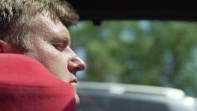 Een mensenslaap in een auto op een reizend hoofdkussen stock videobeelden