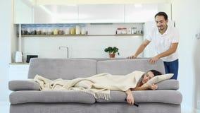Een mensenslaap op de vloer terwijl zijn vrouw op een TV let stock footage