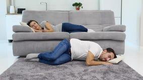 Een mensenslaap op de vloer terwijl zijn vrouw op een TV let stock video
