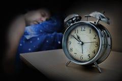 Een mensenslaap op het bed naast de wekker royalty-vrije stock foto
